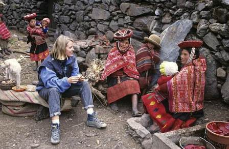 Peru, Huilco, female tourist sitting with woman holding baby, smiling