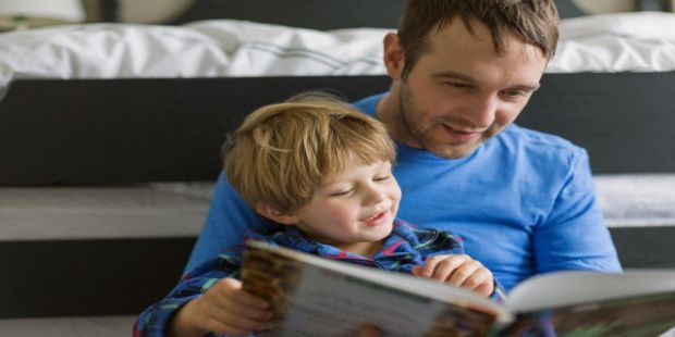 Father reading book to young son.